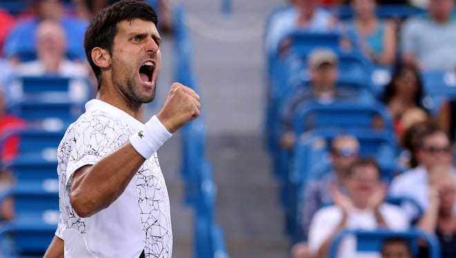 Novak Djokovic, of Serbia, reacts after winning a point against to Milos Raonic, of Canada, during a quarterfinal match of the Western & Southern Open tennis tournament, Friday, Aug. 17, 2018, on center court at the Lindner Family Tennis Center in Mason, Ohio.