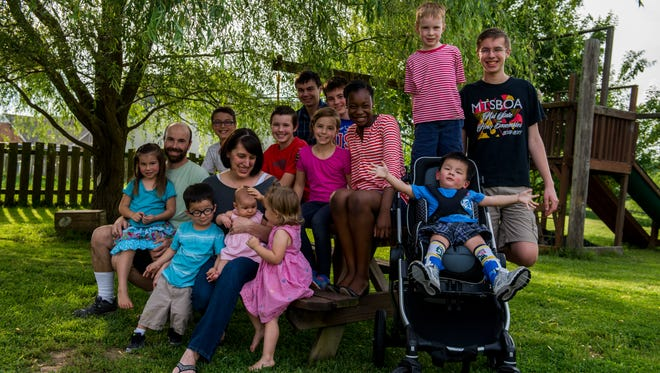Erin Compton, mother of 13, poses for a portrait in her backyard with her family. Pictured are husband Aaron, and kids Trevor, Curtis, Tommy, Alyssa, Mitchell, Bennett, Camille, Russell, Philip, Sophia, Arthur, Caroline and Alexandra.
