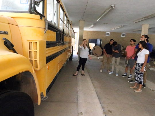 Students in the Bowie Business Academy show a donated district school bus they plan to convert into a food truck.