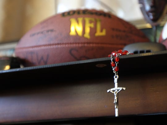 A crucifix from a rosary hangs from a display of Anton