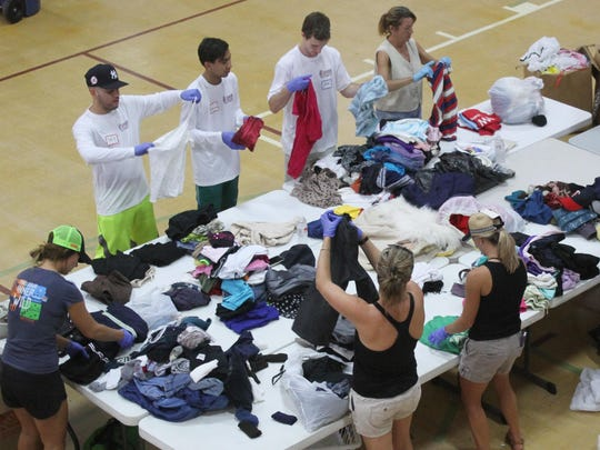Volunteers sort and classify clothing at CityGate Ministries prior to delivering the donated items to various charities on Saturday.