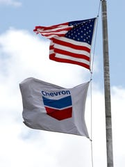 Flags fly outside Chevron on Tuesday at 332 Road 3100 in Aztec.