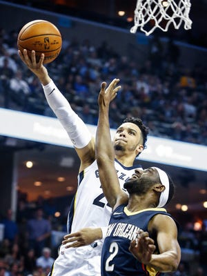 Memphis Grizzlies guard Dillon Brooks (top) drives for a layup against New Orleans Pelicans defender Ian Clark (bottom) during first quarter action at the FedExForum in Memphis, Tenn., Wednesday, October 18, 2017.