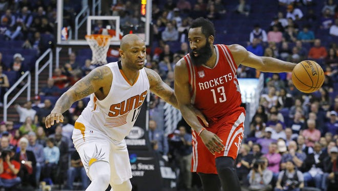 Phoenix Suns forward P.J. Tucker (17) covers Houston Rockets guard James Harden (13) during the second half of their NBA game Wednesday, Dec. 21, 2016 in Phoenix, Ariz.