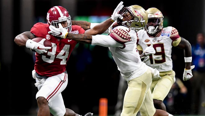 Alabama running back Damien Harris (34) is slowed by Florida State defensive back Derwin James (3) in the Chick-fil-a Classic at the Mercedes - Benz Stadium in Atlanta, Ga., on Saturday September 2, 2017.