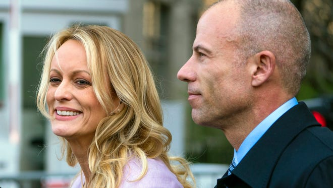 In this April 16, 2018 file photo, adult film actress Stormy Daniels, whose given name is Stephanie Clifford, and her attorney Michael Avenatti talk to reporters outside federal court in New York City.  Daniels has used an online crowdfunding site to raise hundreds of thousands of dollars in her legal case against President Donald Trump. But the unusual method of online fundraising for legal fees raises transparency questions about who is actually supporting her case. Daniels and her attorney, Michael Avenatti, have raised more than $490,000 on the website CrowdJustice.com.  (AP Photo/Craig Ruttle, File)