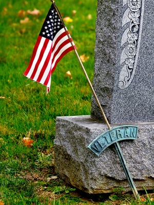 A copper veteran's plaque with an attached American flag honors the grave of Joseph M. Held (1899-1947) Monday at the Poughkeepsie Rural Cemetery located off South Avenue in the Town of Poughkeepsie.