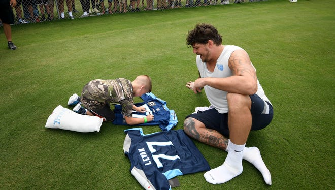 Titans fan Jesse Winger signs a Taylor Lewan jersey for the Titans tackle as the two swap jerseys after practice Sunday at Saint Thomas Sports Park.