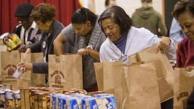 Volunteers from Washington Avenue Baptist Church pack Thanksgiving baskets for Crosslines, an agency of the Council of Churches of the Ozarks. Crosslines and other nonprofits are accepting applications for holiday assistance.