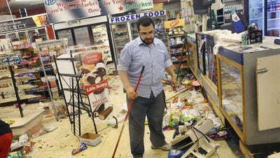 Business owner Mustafa Alshalabi cleans damage to his store, Sam's Meat Market, after it was looted during another night of rioting following protests over the shooting death of Michael Brown on Aug. 16, 2014 in Ferguson, Mo.