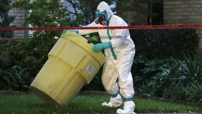 A hazmat worker moves a barrel while cleaning outside the Dallas apartment building of a hospital worker who contracted Ebola. Cincinnati area hospitals, health departments and the airport have been preparing for the possibility of a disease contact here.