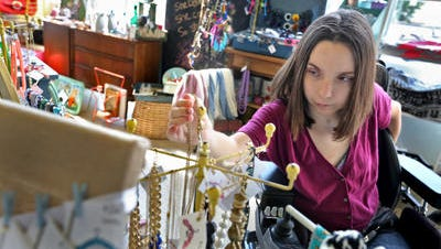 Emily Hunt straightens the merchandise May 28, 2014, at Boomerang BTQ, a boutique where she is a summer intern. She hopes to one day open her own boutique business.