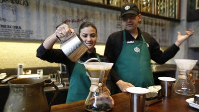 A Starbucks employee demonstrates the preparation of a cup of coffee during a media tour of the new shop in Bogota, Colombia, Wednesday.