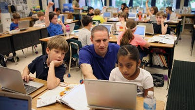 Mike Gray, a third grade teacher at the Cottle School in Tuckahoe, helps students with their assignments on a Chromebook.