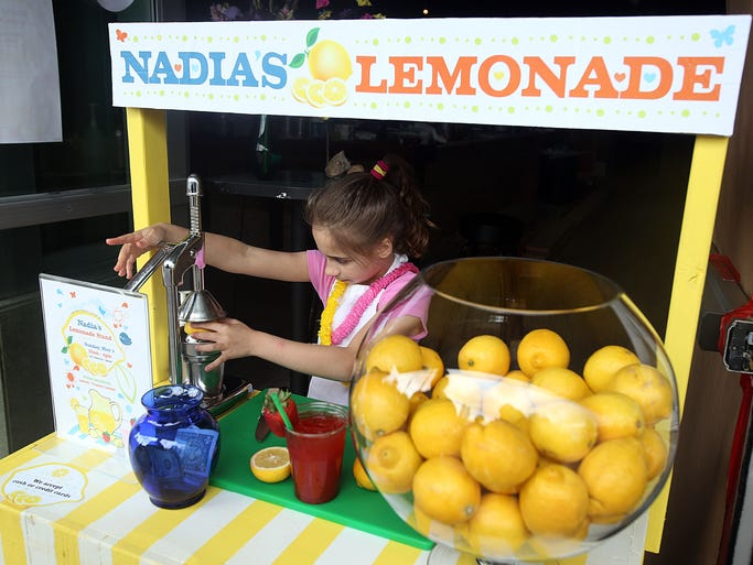 Nadia Knudson squeezes a lemon for fresh strawberry lemonade ordered by a customer. Several lemonade stands are open for business around Salem Sunday, May 4, 2014 as part of Lemonade Day.
