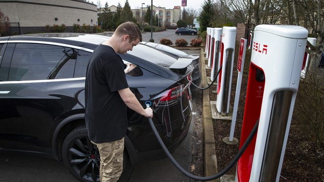 A Tesla driver hooks his vehicle up to a charging station. Gov. Ron DeSantis announced Friday that Florida would spend $8.6 million from a legal settlement with Volkswagon to add 34 fast-charging stations along five state highways.