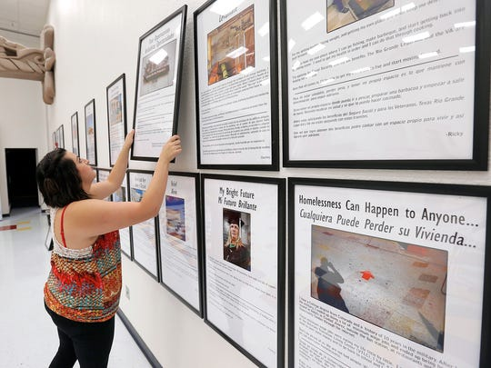 Social worker Courtney Adcox removes the Homeless Photovoice exhibit from La Fe Cultural Center. It is moving it back to UTEP. Adcox joined the project after graduating from UTEP with a social work degree. She experienced homelessness herself while in high school.
