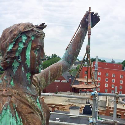The statue of Lady Justice with her scales on top of