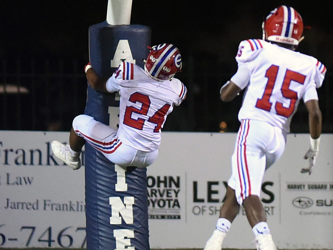 Evangel's Ar'Darius Washington jump on the goal post after scoring a touchdown against Airline in their District 1-5A matchup.