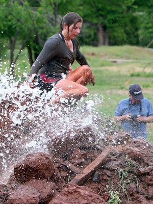 A participant in T.H.O.R. scales one of the two final mud walls as it's being watered down with river water to complete the 5K-ish obstacle run in Lucy Park in 2016. T.H.O.R. returns April 8.