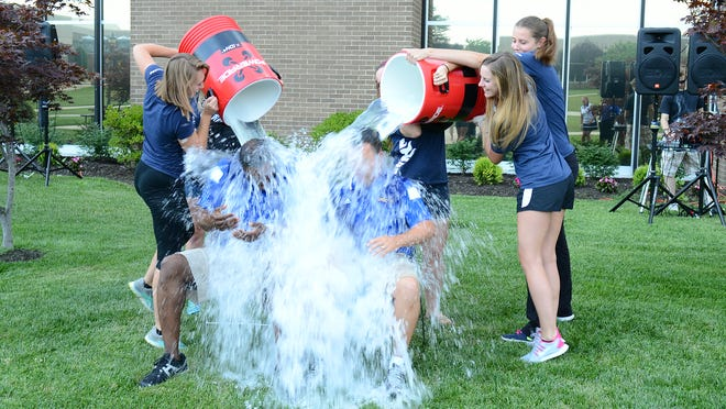 xxx Student athletes: (standing, left to right) Meghan Brown, Bianca Turner, Terra McHenry, Rebecca Pierpont and Kelly Stanton dump containers of ice water on Women's Basketball Head Coach Rich Cooper and Assistant Athletic Director Brian Rowan.