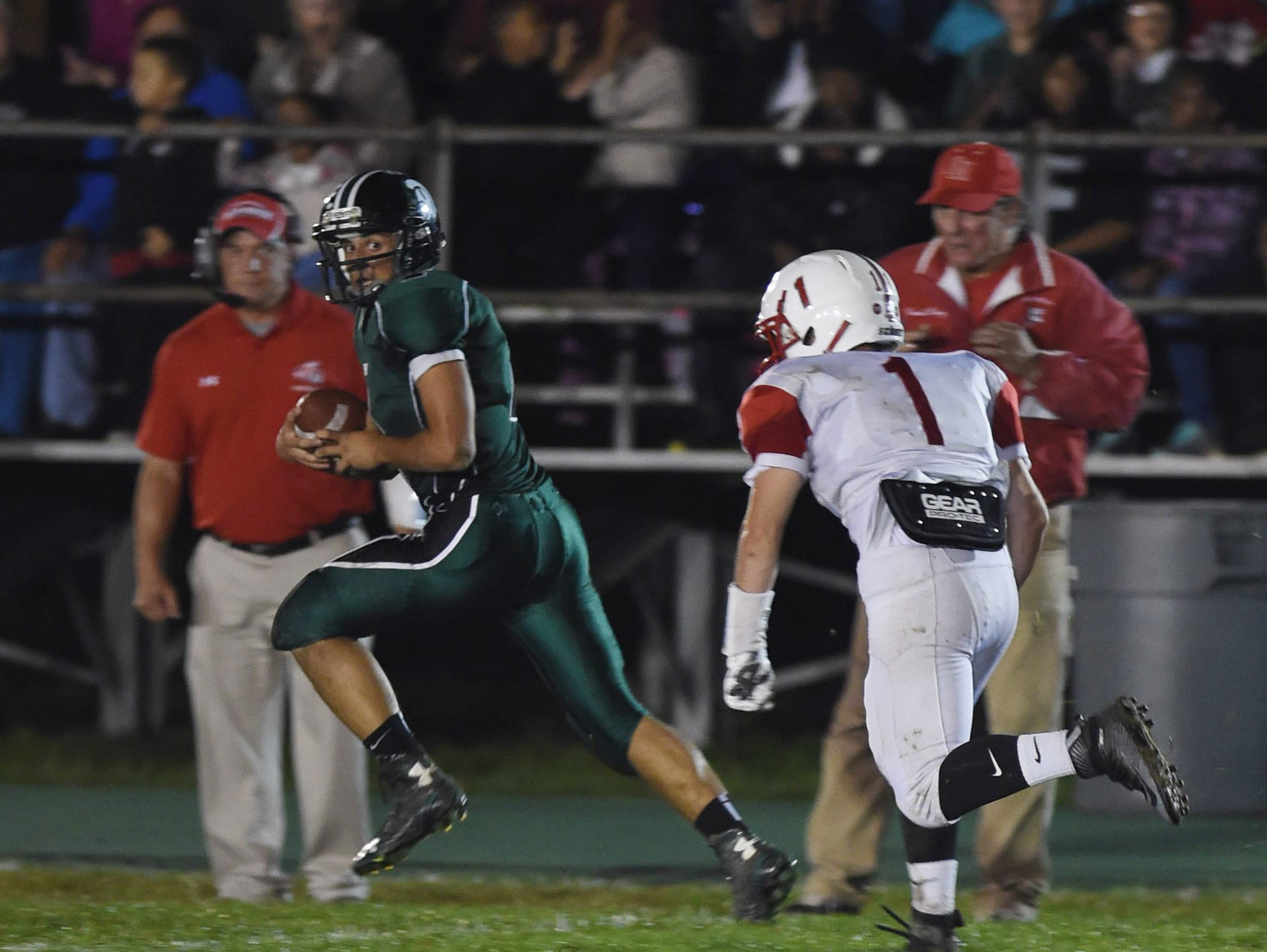 Spackenkill's Joseph Arcuri peeks back at Red Hook's Jimmy Mulvey during his 86 yard touchdown during Friday's game in Poughkeepsie.