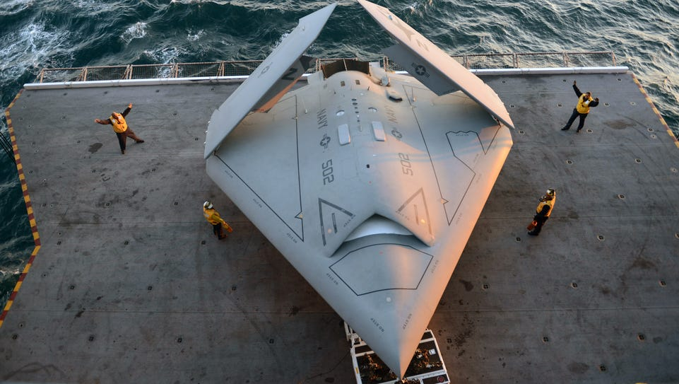 Sailors move an X-47B Unmanned Combat Air System demonstrator