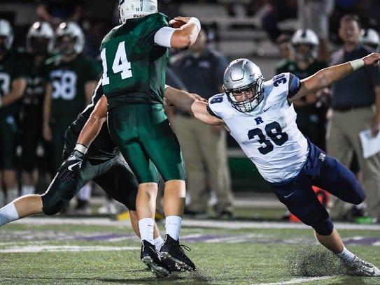 Reitz's Joey Diekmann (38) rushes Catholic quarterback