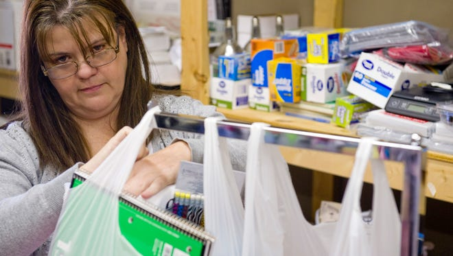 """Barb Bias tops off gift bags with school supplies at God is Good at 425 W. Jennings Street in Newburgh, Ind., Thursday morning. The foundation supplies kids in need with new and """"gently used"""" clothing."""
