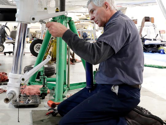 Pete Baumann, lead mechanic and shop inspector with Jet Air Group at Green Bay Austin Straubel International Airport makes repairs on an aircraft Jan. 30, 2018 in Ashwaubenon, Wis. Sarah Kloepping/USA TODAY NETWORK-Wisconsin