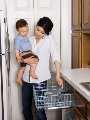 Mother loading dishwasher while holding son and on cell phone