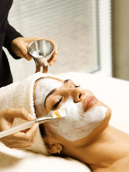 Woman receiving facial treatment at spa