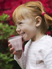 Young girl (5-6) drinking smoothie, smiling