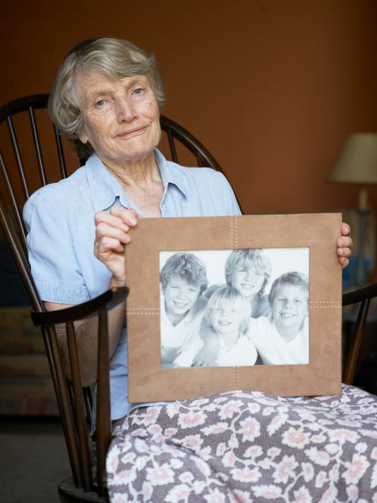Senior Woman At Home Looking At Photo Of Grandchildren