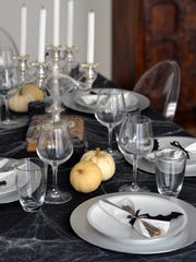 This Halloween table setting uses a black and white minimalistic style.