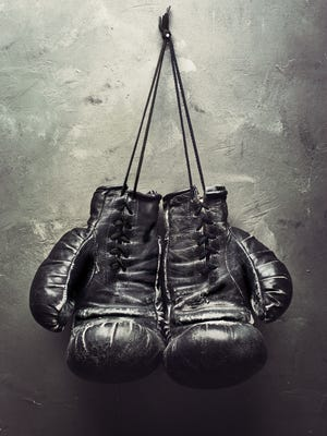 old boxing gloves hang on nail on texturе wall. Retirement concept