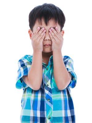 Portrait of boy covering eyes