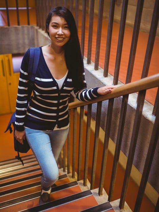 Smiling student walking up steps