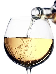 White wine pouring from a bottle to a glass