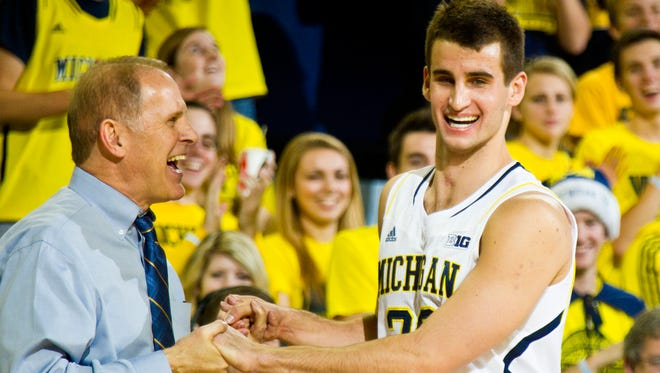 Michigan head coach John Beilein, left, congratulates guard Austin Hatch (30) as he comes off the court in the second half of an NCAA college basketball game against Coppin State at Crisler Center in Ann Arbor, Mich., Monday, Dec. 22, 2014. Michigan won 72-56.