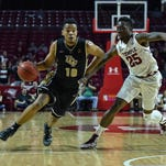 UCF Knights guard Adonys Henriquez moves the ball up court as Temple Owls guard Quenton DeCosey defends during the first half of the game at Liacouras Center.