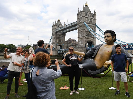 People pose in front of a statue of actor Jeff Goldblum