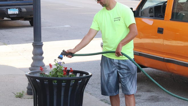 City of Pontiac employee Kevin Folk provides a little refreshment for some flowers downtown Thursday morning.