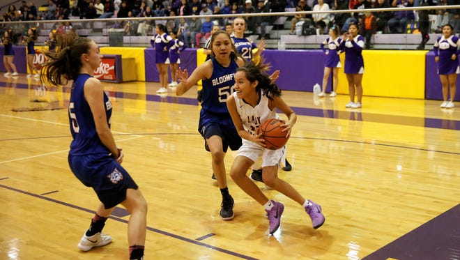 Kirtland Central's Haile Gleason, No. 10 in white, drives along the baseline toward the basket against Bloomfield's Alyssa Quintana, No. 50 in blue, and Mattie Waresback (5) during a District 1-5A game on Thursday, Feb. 15 at Bronco Arena. Both teams will host first-round playoff games.