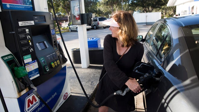 "Angie Pugliese pumps gas at the Marathon gas station on the corner of Davis and Collier Boulevard late Wednesday afternoon in East Naples. ""It jumped up 50 cents in a day,"" Pugliese said. Gas prices jumped significantly in places throughout the county  Wednesday."