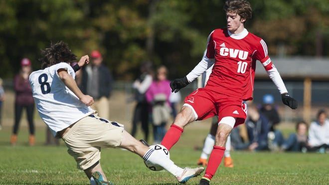 Essex's Kirk Teare (8) slides tackles CVU's Cooper O'Connell (10) during a high school boys soccer game in Essex on Saturday.