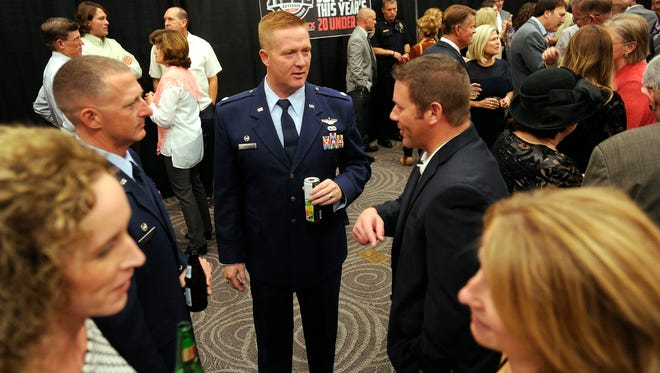 Lt. Col. Michael Hanson (center), a 20 Under 40 recipient, talks with friends during the reception prior to 20 Under 40 dinner on Thursday at the Abilene Civic Center.