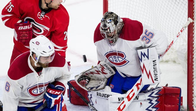 Montreal Canadiens goalie Charlie Lindgren (35) stops the puck as The Carolina Hurricanes' Chris Terry (25) and Canadiens' Greg Pateryn (6) skate in front of the net during the third period on April 7 in Raleigh, N.C. Montreal won 4-2.