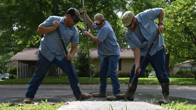 Mountain Home Water and Sewer Department workers Luke McDole, left, James May, center, and Garrett Bowling, right, dig up a broken water line on South Street late Thursday afternoon. The department is working to eliminate leaks that are causing a substantial loss of the city's potable water.