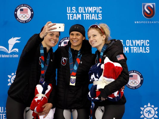 Second place finisher Heather Bergsma, left, takes selfie with first place finisher Brittany Bowe, center, third place finisher Mia Manganello, right, during a medal ceremony following women's 1,500 meters during the U.S. Olympic long track speedskating trials, Saturday, Jan. 6, 2018, in Milwaukee. (AP Photo/John Locher)